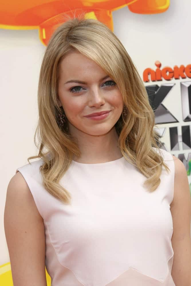 Emma Stone was at the 2012 Nickelodeon Kids' Choice Awards held at the Galen Center in Los Angeles, CA on March 31, 2012. She paired her simple white outfit with an elegant layered blond hairstyle with a tousle and waves.