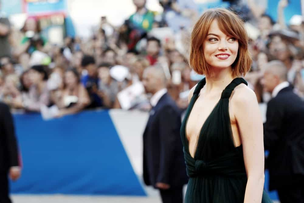 Actress Emma Stone attended the 'Birdman' premiere during the 71st Venice Film Festival at Palazzo Del Cinema on August 27, 2014 in Venice, Italy. She was quite the stunner in her dark green dress and short tousled red hairstyle with bangs.