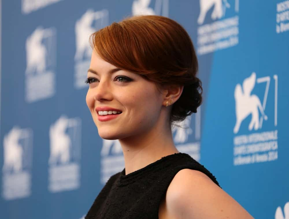 """On August 27, 2014, Emma Stone was at the photocall of the film """" Birdman """" during the 71th Venice Film Festival 2014 in Venice, Italy. She paired her simple black outfit with an elegant and stylish low bun hairstyle with side-swept bangs."""