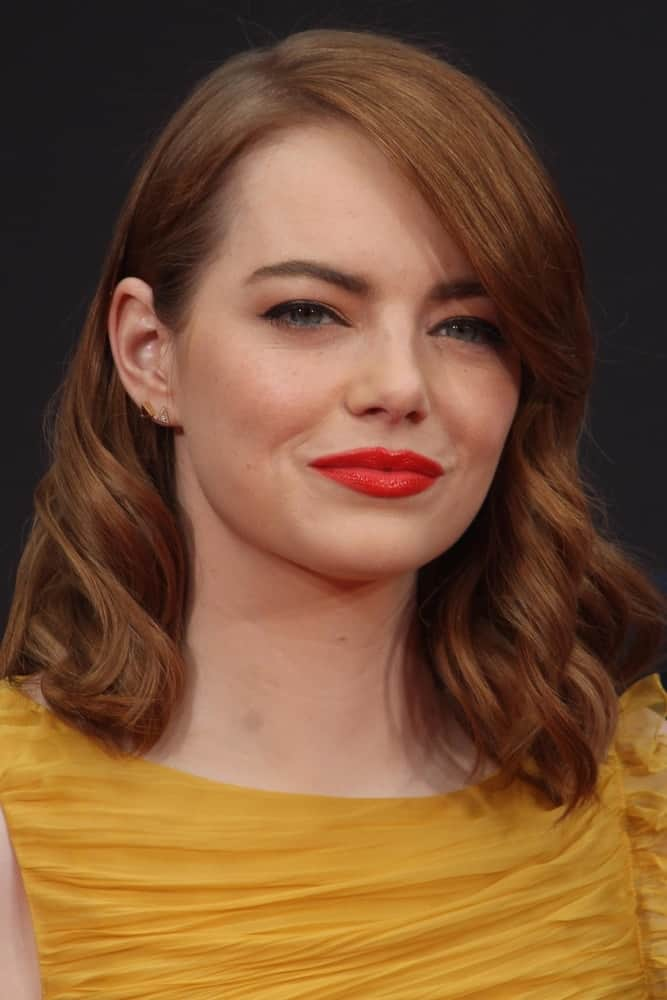 Emma Stone, along with Ryan Gosling, was honored with a Hand and Foot Print Ceremony at TCL Chinese Theater on December 7, 2016 in Los Angeles, CA. She was lovely in her yellow cocktail dress that she paired with long and wavy red hair