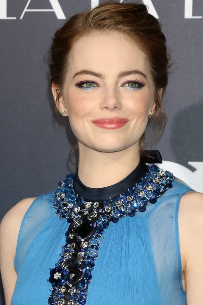 "Emma Stone was at the ""La LA Land"" World Premiere at Village Theater on December 6, 2016 in Westwood, CA. She paired her elegant messy bun hairstyle with a gorgeous blue sheer dress with details"