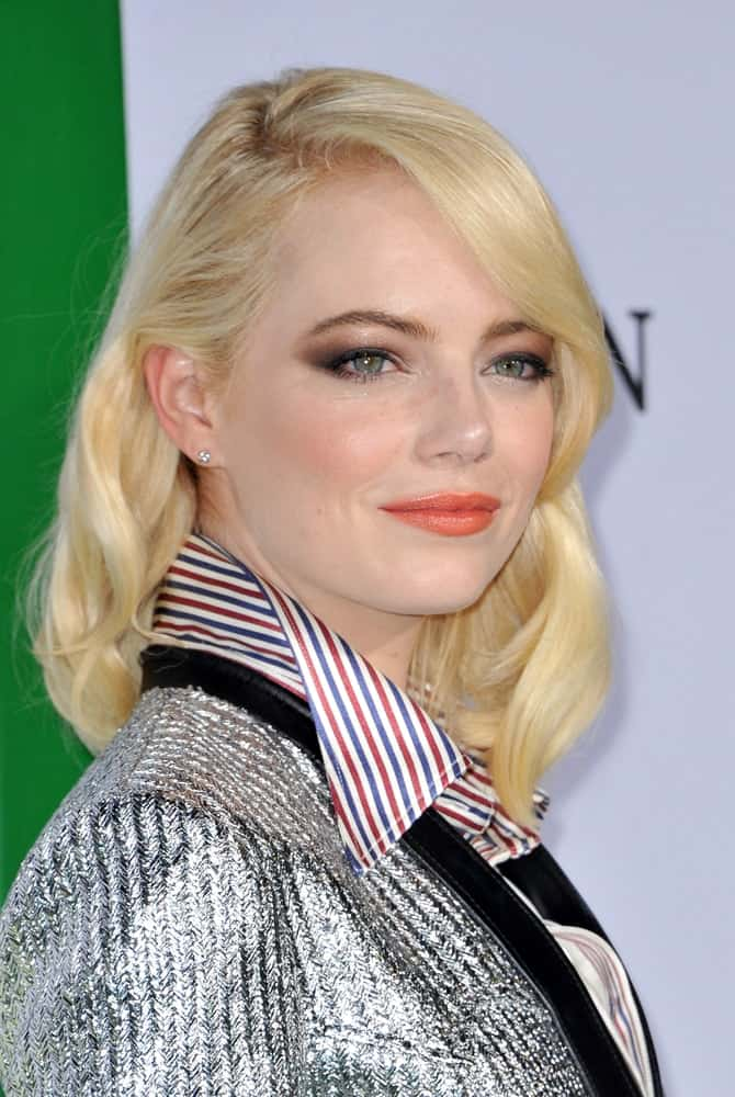 A very blond Emma Stone attended the Los Angeles premiere of 'Battle of the Sexes' held at the Regency Village Theatre in Westwood on September 16, 2017. She wore a silver outfit to go with her shoulder-length wavy layers.