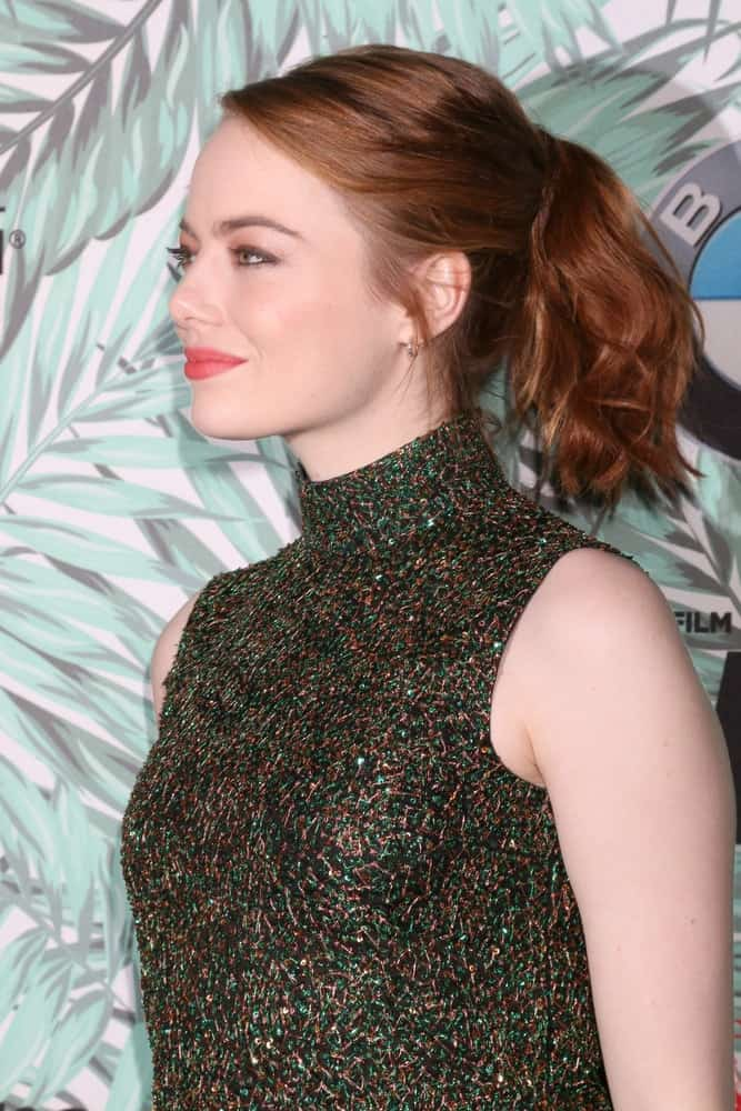 Emma Stone's colorful stunning dress went perfectly well with her messy ponytail hairstyle with waves and a tousle at the 10th Annual Women in Film Pre-Oscar Cocktail Party at Nightingale Plaza on February 24, 2017, in Los Angeles, CA.