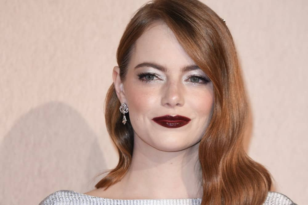 "On October 18, 2018, Emma Stone was at the London Film Festival screening of ""The Favourite"" at the BFI South Bank, London. She flaunted her lovely lips with some dark make-up and a pinned side-swept hairstyle with waves."