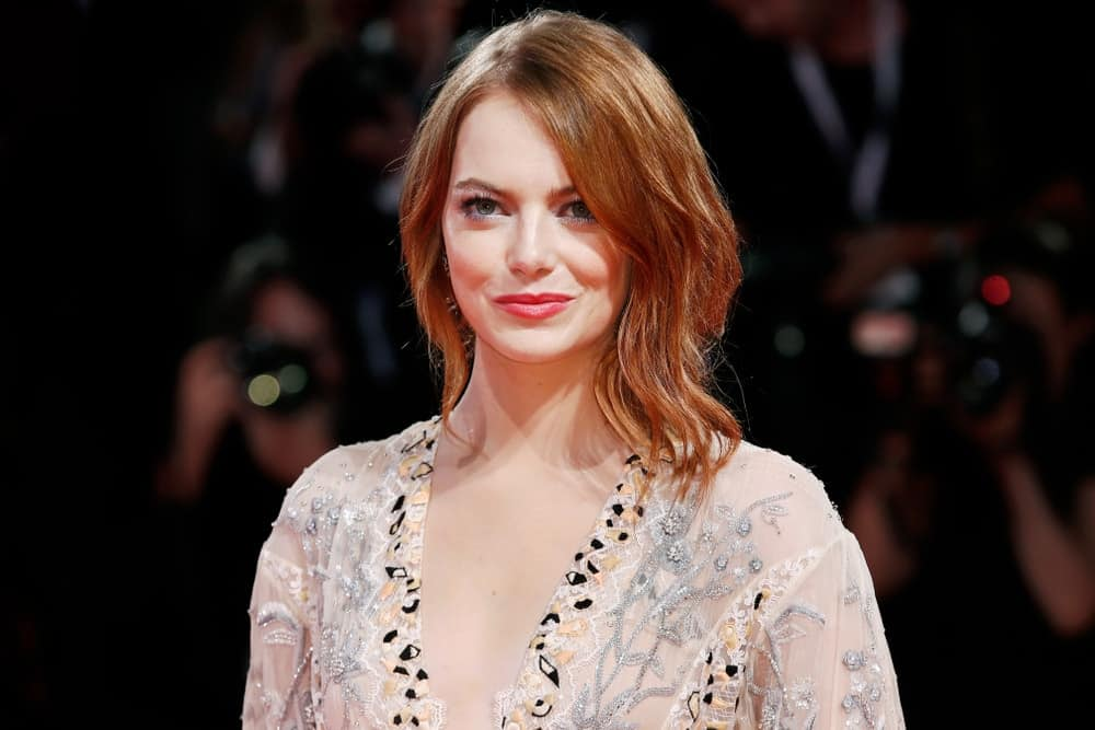 Emma Stone looked quite sophisticated and stunning in the detailed sheer dress that she paired with her gorgeous loose red hair with subtle waves at the red carpet of the movie 'The Favourite' during the 75th Venice Film Festival on August 30, 2018, in Venice, Italy.