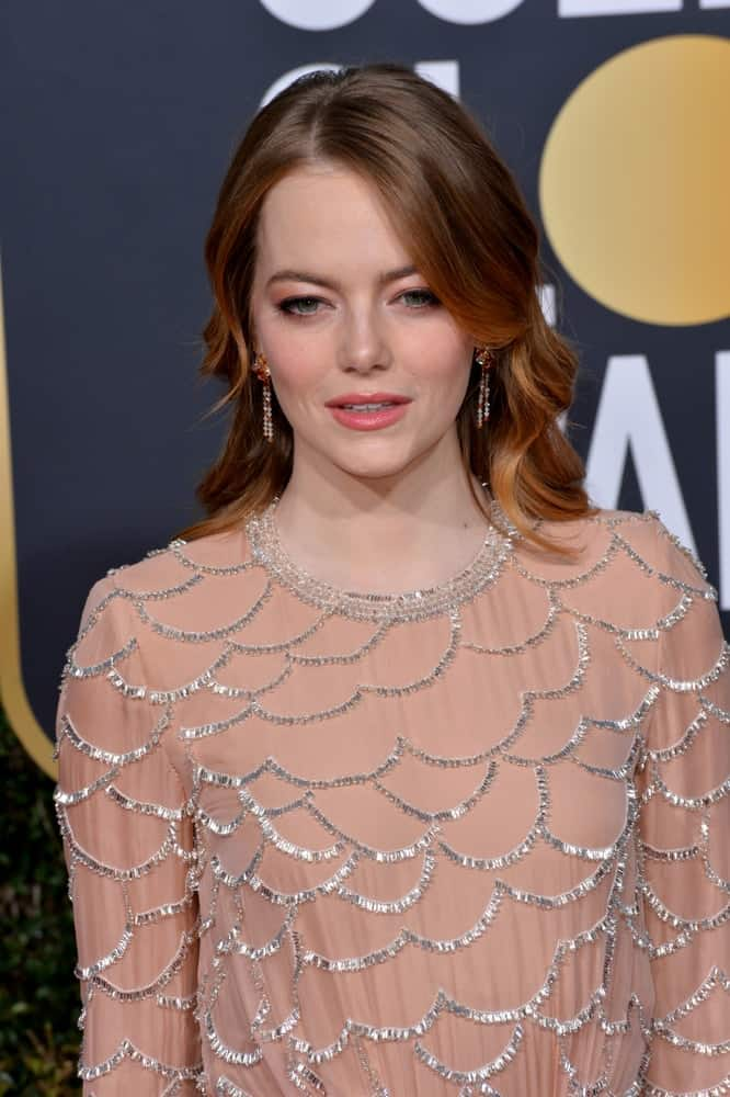 On January 06, 2019, Emma Stone attended the 2019 Golden Globe Awards at the Beverly Hilton Hotel. She wore an elegant blush dress with silver details to pair with her highlighted and layered wavy hairstyle.