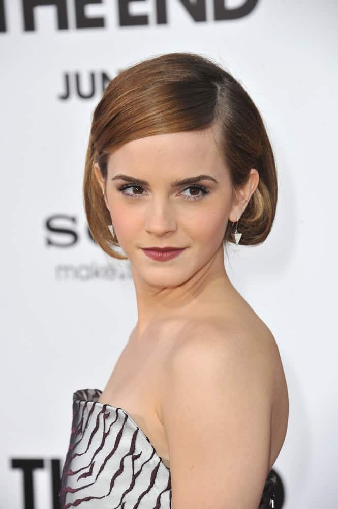 "Emma Watson was at the world premiere of her movie ""This Is The End"" at the Regency Village Theatre on June 3, 2013, in Los Angeles, CA. She paired her short side-swept pinned half-up hairstyle with a fashionable patterned outfit."
