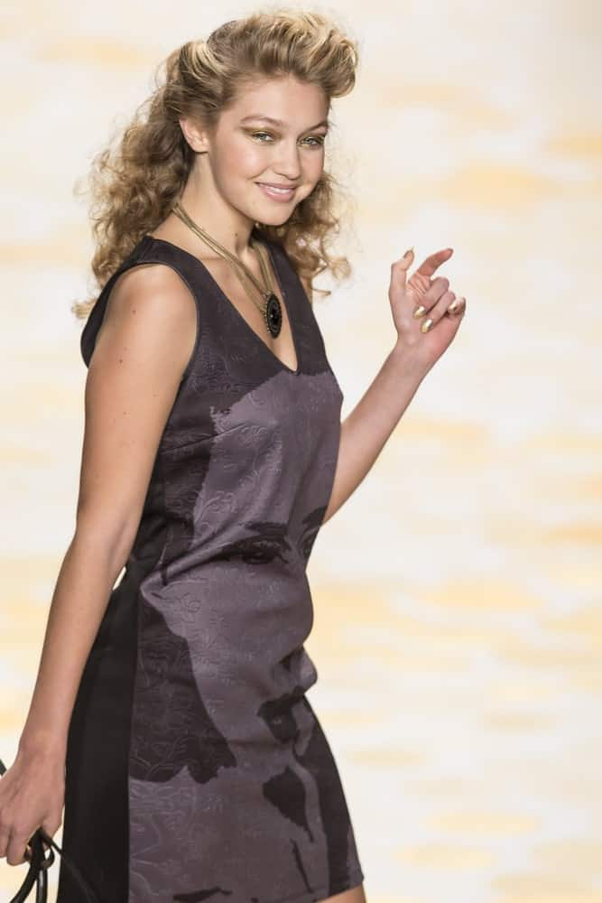 On February 6, 2014, Gigi Hadid walked the runway during the Desigual fall 2014 fashion show at New York Mercedes – Benz Fashion Week. Her hair was a vintage half up curly hairstyle.