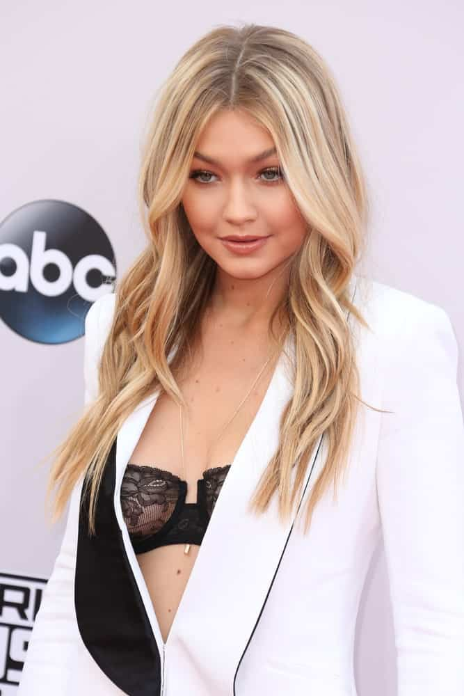 Gigi Hadid's long highlighted hair was center-parted and wavy at the 2014 American Music Awards – Arrivals at the Nokia Theater on November 23, 2014, in Los Angeles, CA.