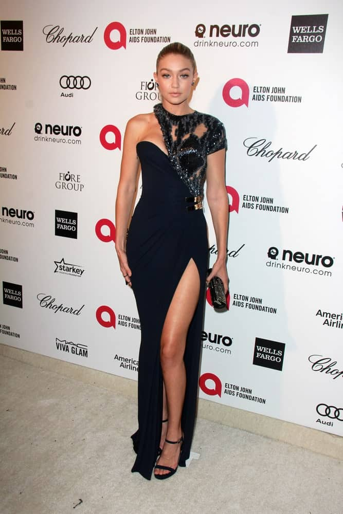 Gigi Hadid wore a stunning long black dress that emphasizes her long legs paired with a slick bun hairstyle at the Elton John Oscar Party 2015 at the City Of West Hollywood Park on February 22, 2015, in West Hollywood, CA.