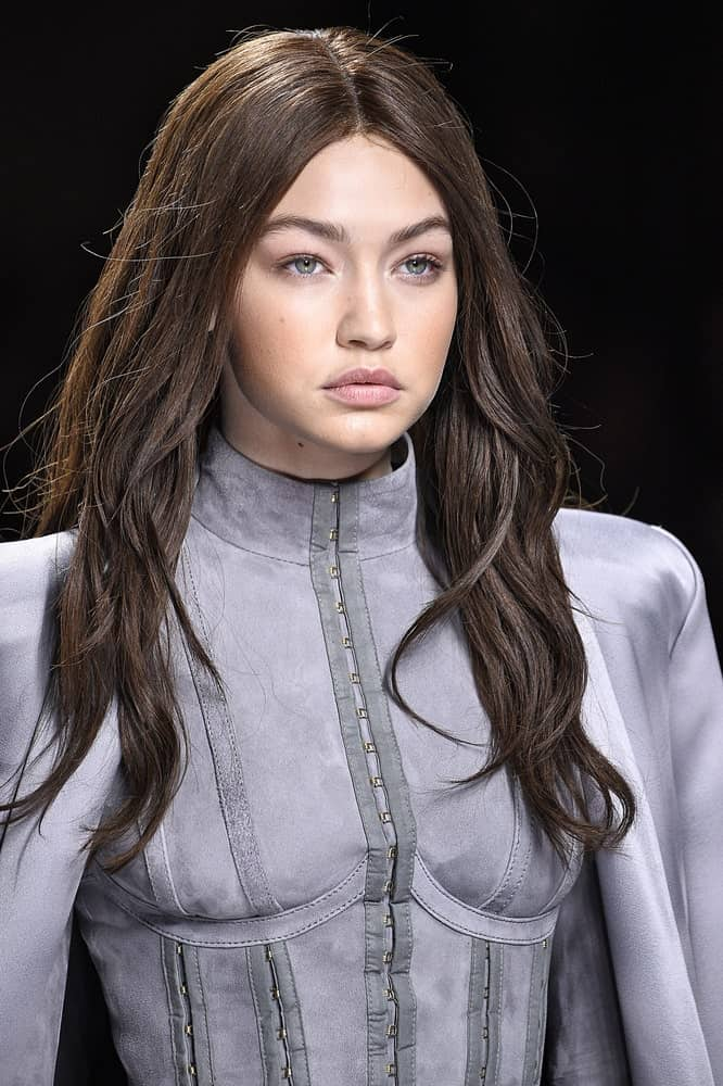 Gigi Hadid was dressed in a detailed gray dress to go with her loose and tousled dyed dark hairstyle at the runway during the Balmain show on March 3, 2016, in Paris, France.