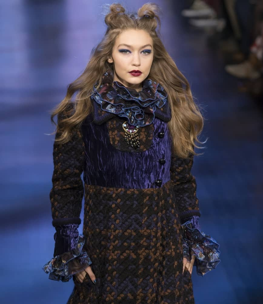 Gigi Hadid walked the runway at the Anna Sui Fall Winter 2017 fashion show during New York Fashion Week on February 15, 2017. She wore a detailed dress to go with her half-up hairstyle that has two small buns to imitate cat ears.
