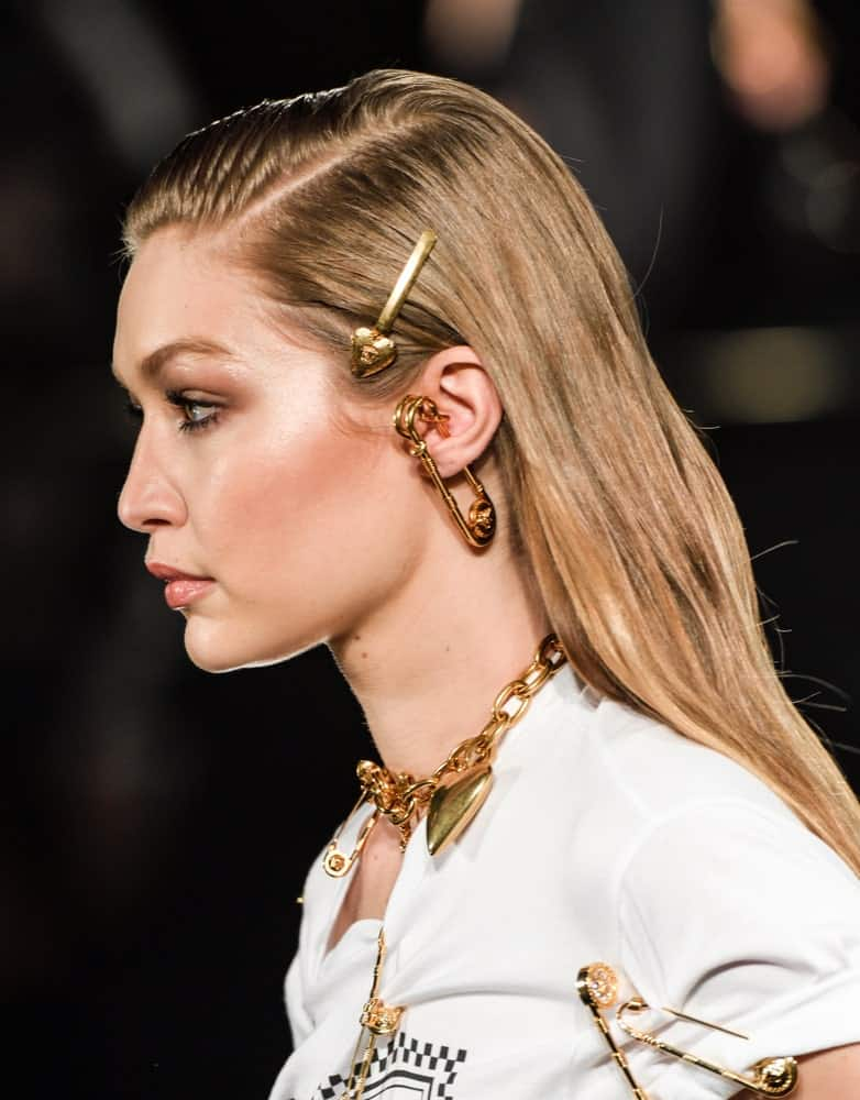 On December 2, 2018, Gigi Hadid walked the runway at the Versace Pre-Fall 2019 Collection at The American Stock Exchange. Her hair was styled with pins into a slick half-up hairstyle with subtle highlights.