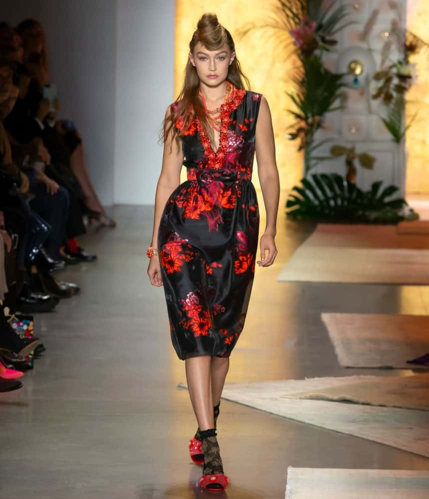 On September 10, 2018, Gigi Hadid walked the runway at the Anna Sui Spring Summer 2019 fashion show during New York Fashion Week. Her hair was styled into a unique half-up hairstyle with a bun at the bangs.