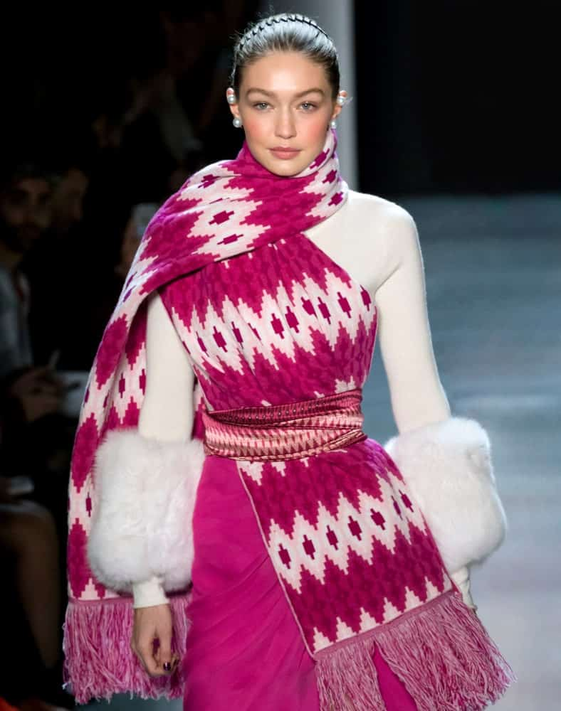On February 11, 2018, Gigi Hadid walked the runway at the Prabal Gurung Fall Winter 2018 fashion show during New York Fashion Week. She was dressed in pink and white to go with her upstyle hair with a hairband.