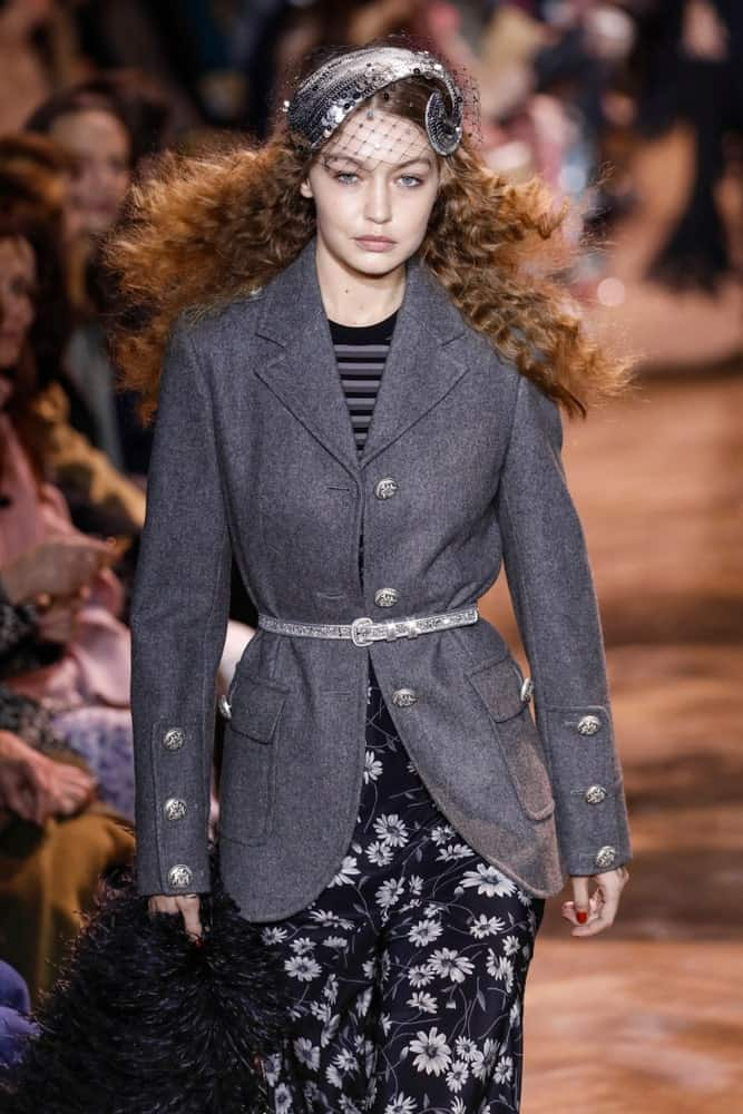 Gigi Hadid walked the runway at the Michael Kors fashion show during New York Fashion Week on February 13, 2019, in New York City. Hadid's Hair was styled with a curly loose finish and fitted with a quirky headdress.