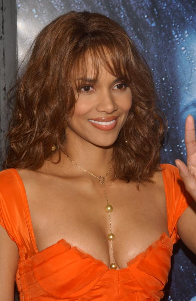 Actress Halle Berry paired her lovely orange dress with a tousled wavy shoulder-length hairstyle with wispy bangs and a reddish tone at the world premiere of her new movie Gothika in Hollywood on November 13, 2003.