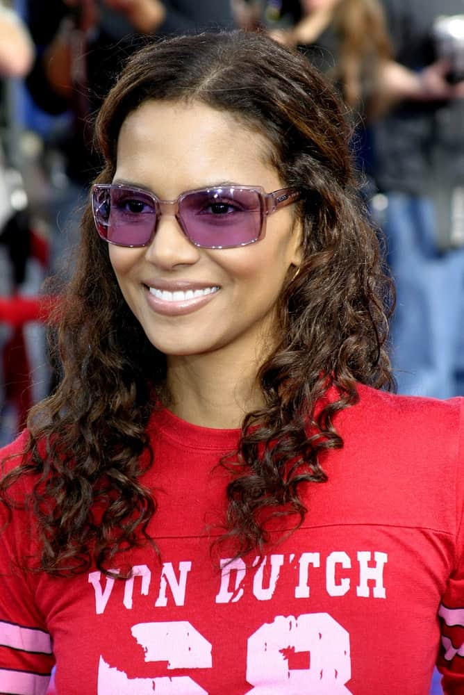 "Halle Berry attended the Los Angeles Premiere of ""Robots"" held at the Mann Village Theatre in Westwood, California on March 6, 2005. She came wearing a casual Von Dutch shirt to match her half-up curly hairstyle and cool colored sunglasses."