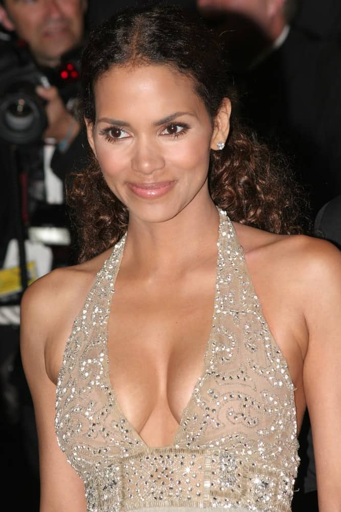 Halle Berry wore an elegant gown to match with her long and curly half-up hairstyle at the 'X-Men 3' premiere at the Palais des Festivals during the 59th Cannes Film Festival on May 22, 2006, in Cannes, France.