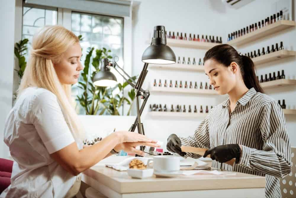 A woman having her nails done in a salon.