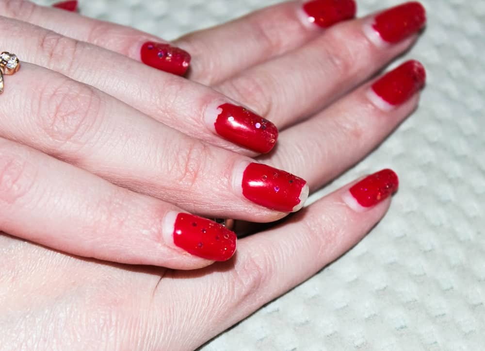 Shabby old red nail polish with glitters.