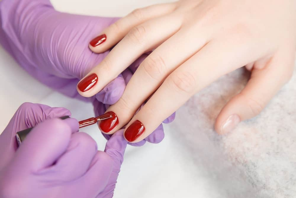 A woman having her nails done in a salon with a red finish.