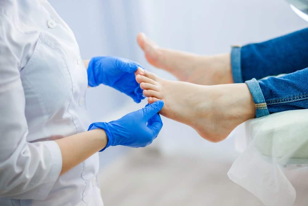 A healthcare professional examining a foot of a patient.