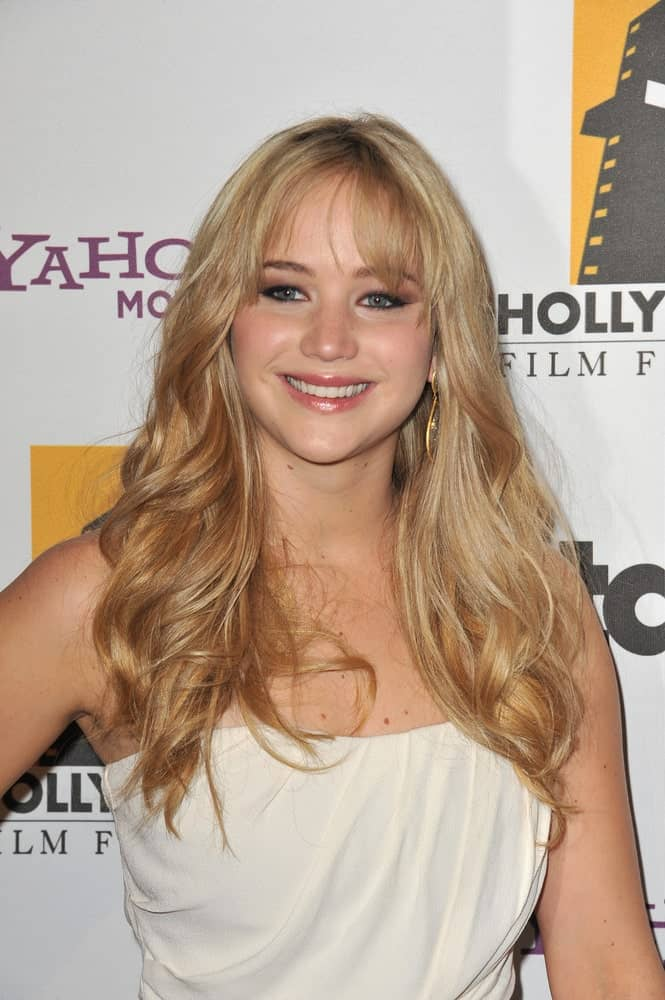 Jennifer Lawrence's long, layered and highlighted sandy blond hair was complemented with wispy bangs and a white strapless dress at the 14th Annual Hollywood Awards Gala at the Beverly Hilton Hotel on October 25, 2010, in Beverly Hills, CA.