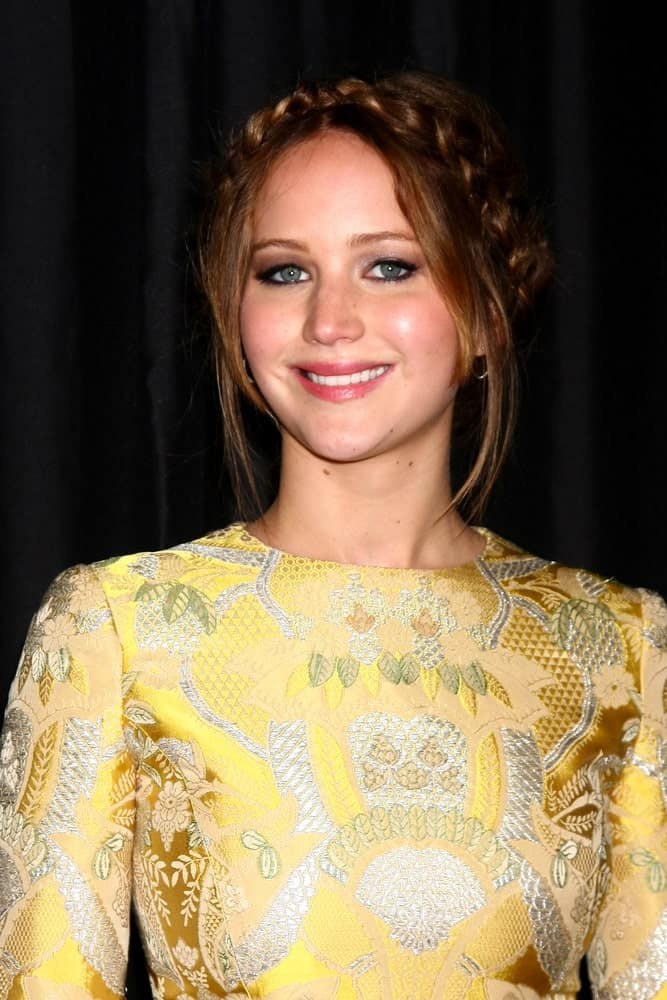 Jennifer Lawrence wore a patterned and detailed yellow outfit with her crown braid hairstyle incorporated with loose tendrils when she arrived at the 2013 LA Film Critics Awards at InterContinental Hotel on January 12, 2013, in Century City, CA.