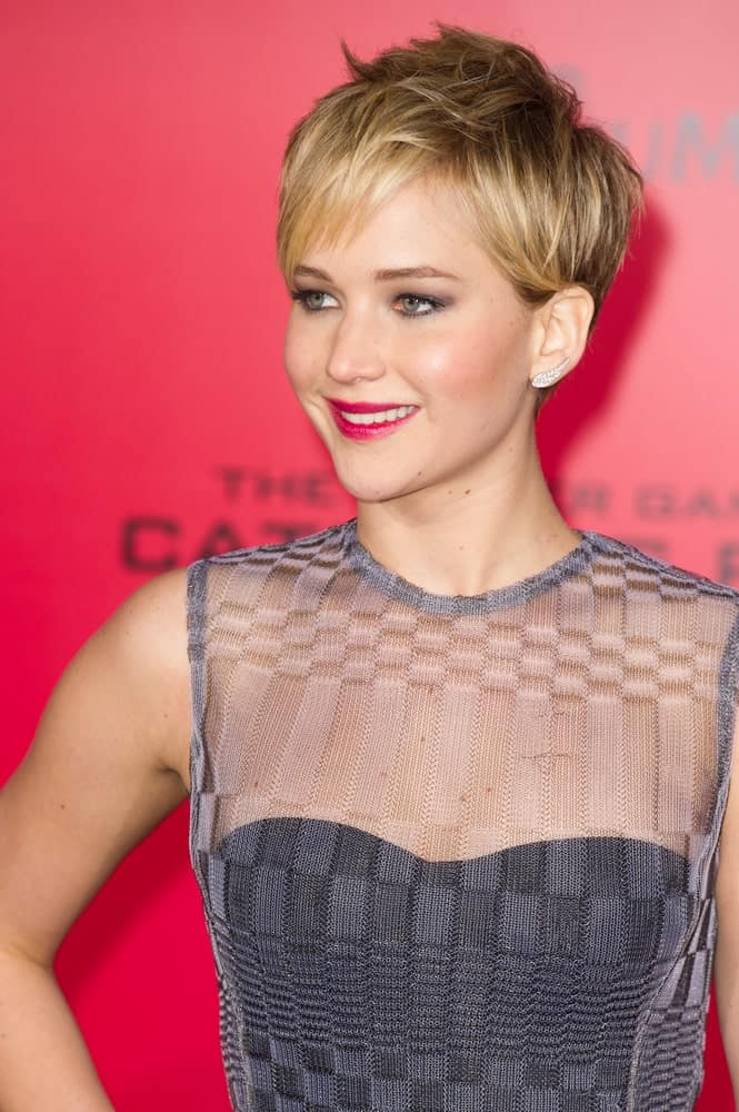 Actress Jennifer Lawrence's fashionable and stylish dress worked quite well with her tousled blond pixie hairstyle with a slight spiky finish at the premiere of The Hunger Games: Catching Fire at the Nokia Theater in Los Angeles, CA on November 18, 2013.