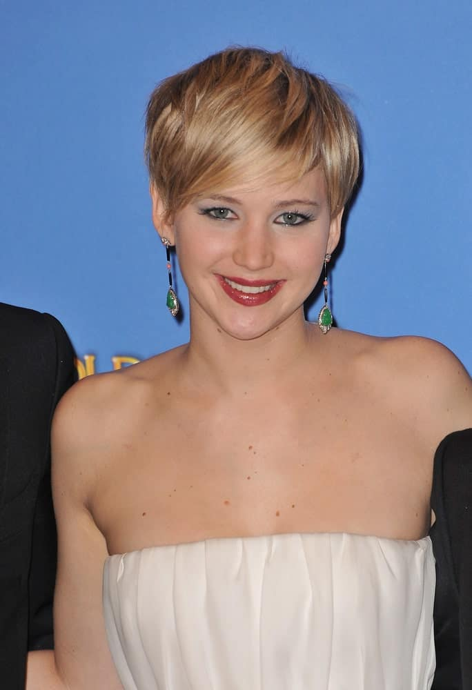 On January 12, 2014, Jennifer Lawrence highlighted her neckline and lovely earrings with a strapless white dress and a blond pixie hairstyle with long side-swept bangs in the press room at the 71st Annual Golden Globe Awards.