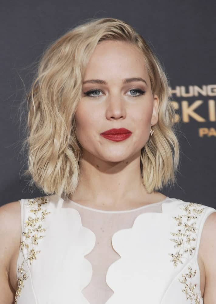 Jennifer Lawrence attended the Los Angeles premiere of 'The Hunger Games: Mockingjay – Part 2' held at the Microsoft Theater in Los Angeles, USA on November 16, 2015. She wore a sweet white dress with floral details to match her loose and tousled side-swept wavy bob hairstyle.