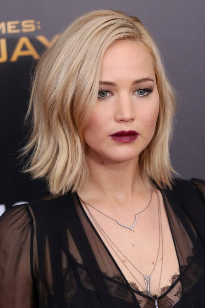 "Jennifer Lawrence went with bold lips and black sheer dress to go with her platinum blond side-swept wavy bob hairstyle at the premiere of ""The Hunger Games: Mockingjay – Part 2"" at AMC Lincoln Square on November 18, 2015, in New York City."
