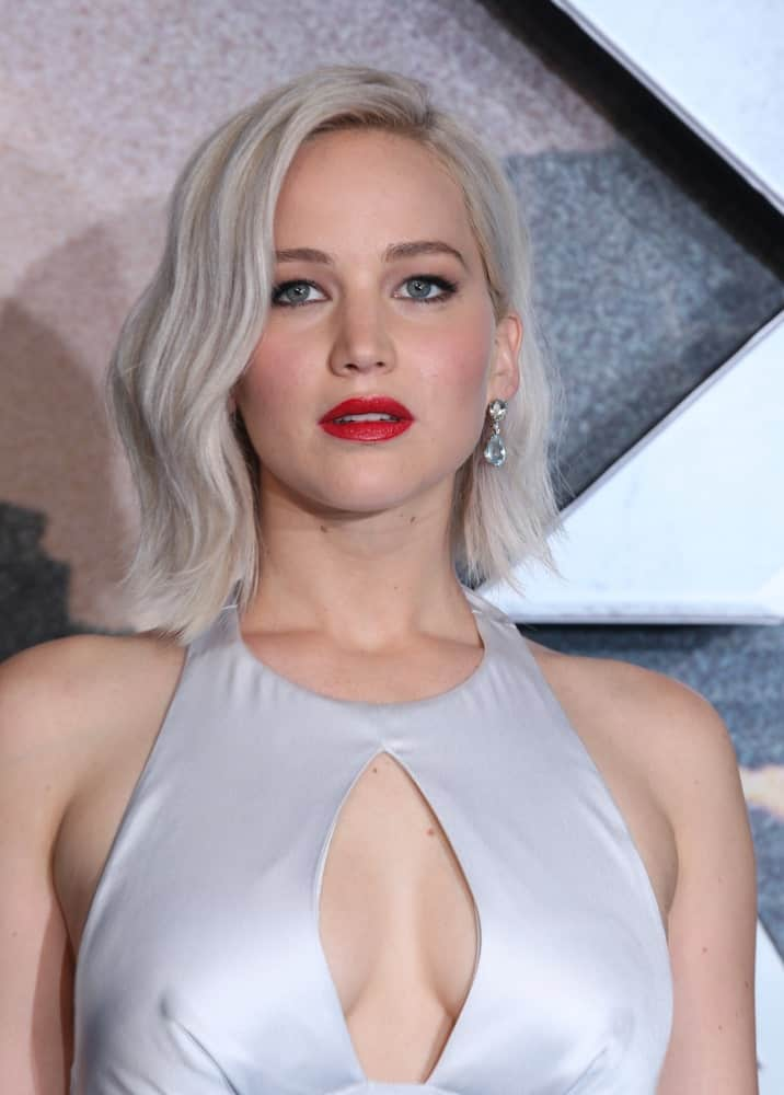 Jennifer Lawrence paired her pearly white dress with a platinum blond side-swept wavy bob hairstyles when she attended the X-Men: Apocalypse – UK fan screening at the BFI IMAX on May 9, 2016, in London.