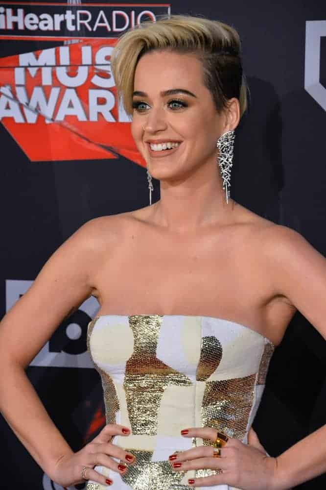 Katy Perry's appearance marks at the 2017 iHeartRadio Music Awards because of her dramatic new pixie cut side-swept hairstyle and a stunning strapless metallic Getty Atelier dress that's actually a pantsuit! No wonder why she's the crowd's favorite that day!