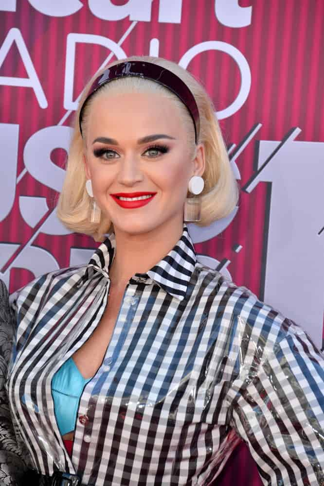 Katy Perry slicked back her short blonde hair with a black headband during the 2019 iHeartRadio Music Awards at the Microsoft Theatre on March 14, 2019. Statement earrings and a plaid top completed the vintage look.