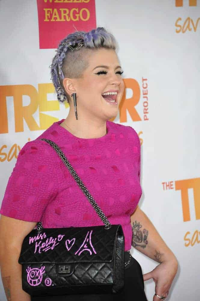 A bold look by Kelly Osbourne during the 2014 TrevorLIVE Los Angeles Gala at the Hollywood Palladium. She wears a purple T-shirt and a violet braided hairstyle. Photo taken on the 7th of December.