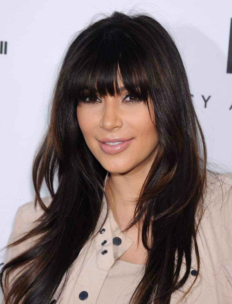 Kim Kardashian incorporates her long layered locks with eye-skimming bangs during the Tracy Anderson Flagship Studio Opening on April 04, 2013, in Hollywood, CA.