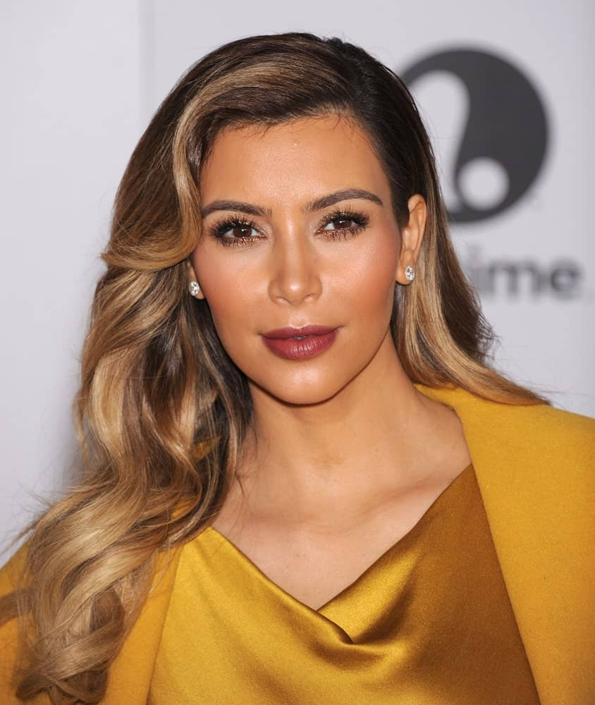Kim Kardashian displayed her side-swept glam waves in blonde with dark roots at the Entertainment Breakfast 2013 on December 11, 2013. She finished the look with a gold gown and stud earrings.