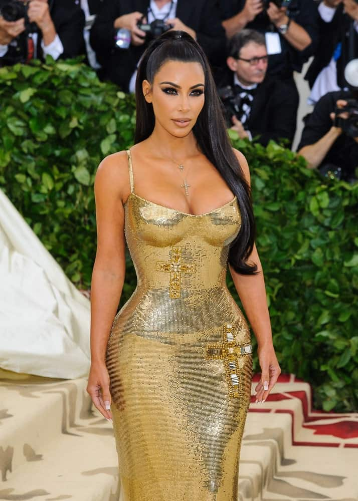 """Kim Kardashian arrived for the 2018 Metropolitan Museum of Art Costume Institute Gala: """"Heavenly Bodies: Fashion and the Catholic Imagination"""" on May 7, 2018, with a sky-high ponytail complemented with a stunning gold gown."""