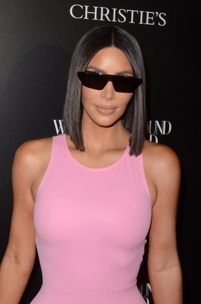 Kim Kardashian looking sleek in her bob cut that's complemented with black shades and a pink dress at the Christie's X 25th Anniversary Auction Preview at the What Goes Around Comes Around on August 21, 2018.