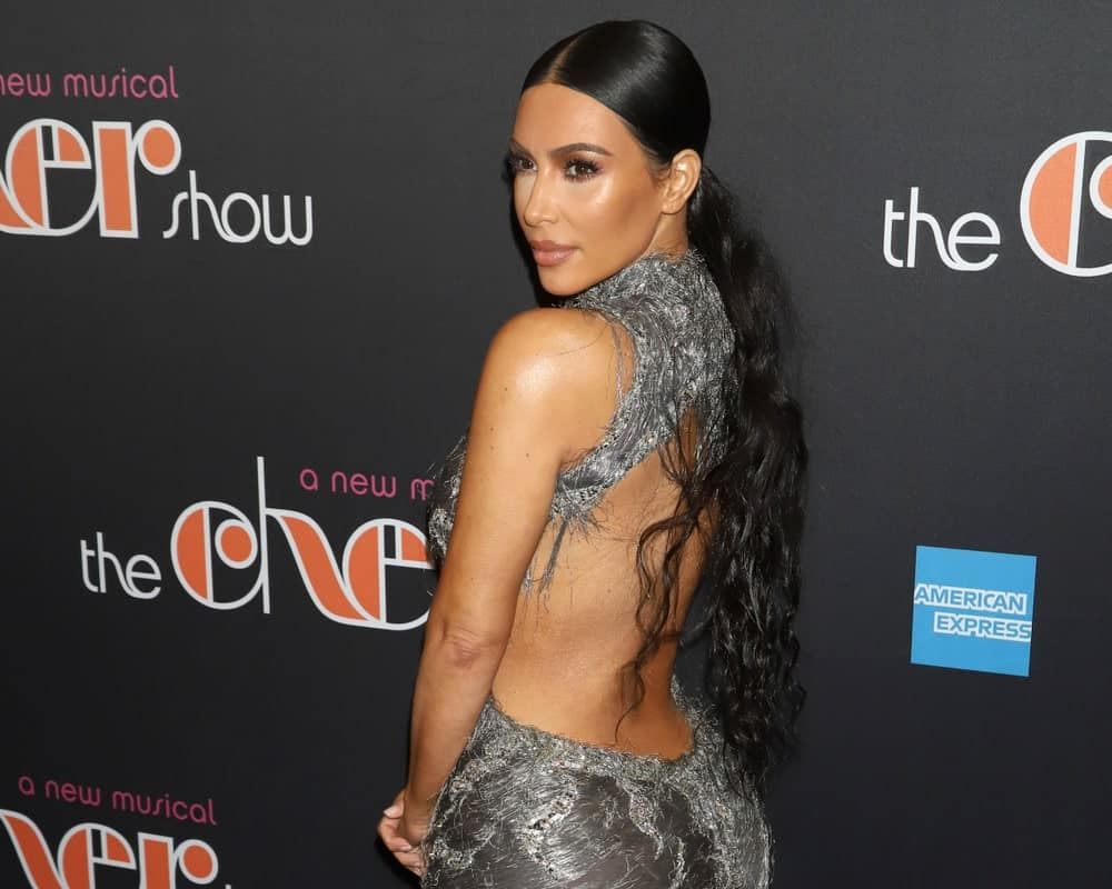 """Kim Kardashian wore a sexy backless gown that goes along her low curly ponytail at the Broadway opening night of """"The Cher Show"""" on December 3, 2018."""