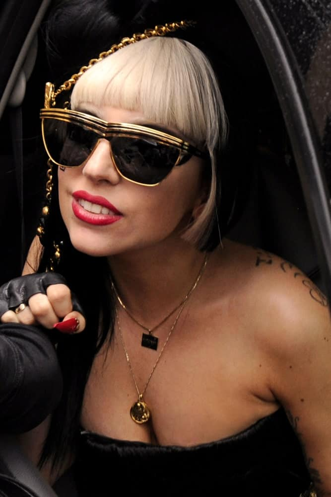 "Pop superstar Lady Gaga greeted her ""Little Monster"" fans while leaving the View television show outside ABC Studios on May 23, 2011, in New York City. She was stunning in her black strapless dress that went well with her cool sunglasses and unique hairstyle that has blunt bangs and partly dyed blond."