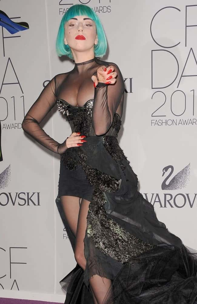 Lady Gaga was at the 2011 CFDA Fashion Awards held at the Alice Tully Hall in Lincoln Center, New York on June 6, 2011. She came in a fashionable long sheer black dress that she topped with colorful make-up and a short blue bob hairstyle with blunt bangs.