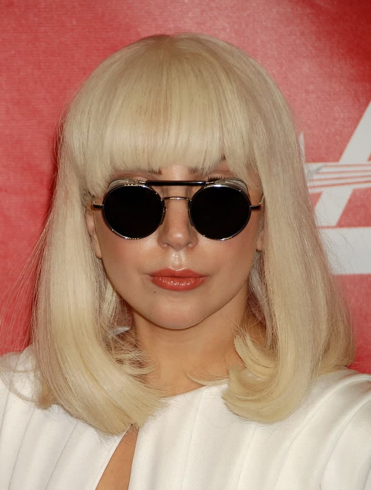 Lady Gaga went with a classy shoulder-length bob hairstyle that has blunt bangs to go with her white dress at the 2014 MusiCares Person Of The Year Honoring Carole King on January 24, 2014, in Los Angeles, CA.