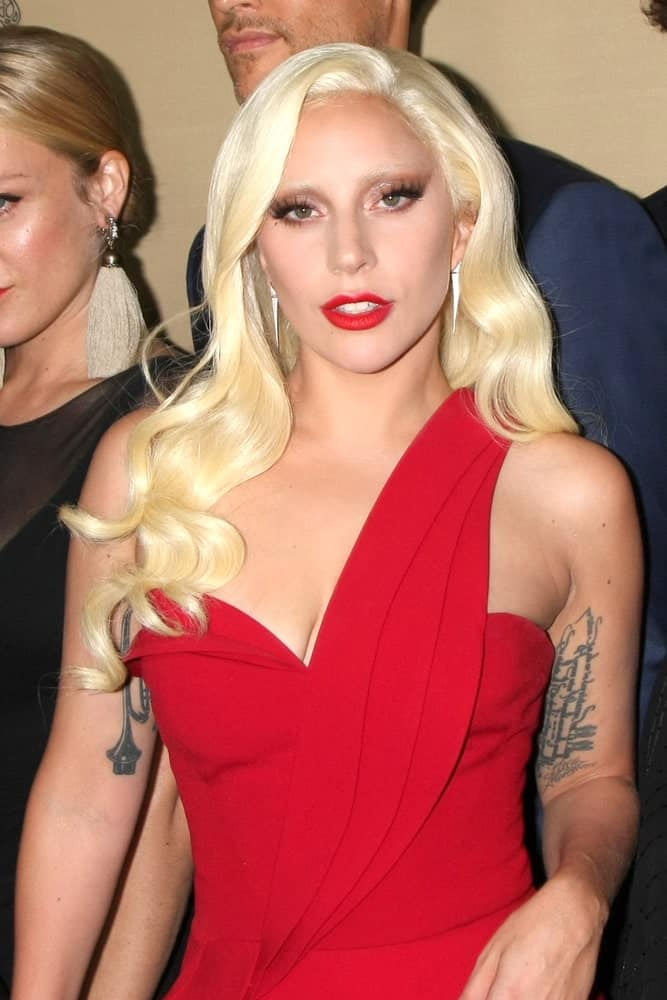 "Lady Gaga channeled a little bit of Jessica Rabbit with her lovely red dress, red lips and alluring long wavy side-swept blond hair at the ""American Horror Story: Hotel"" Premiere Screening at the Regal 14 Theaters on October 3, 2015, in Los Angeles, CA."