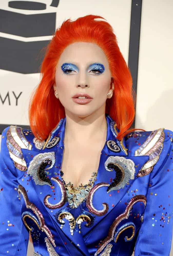 Lady Gaga wore a red-orange dyed hairstyle that contrasts her blue marching band jacket at the 58th GRAMMY Awards held at the Staples Center in Los Angeles on February 15, 2016.