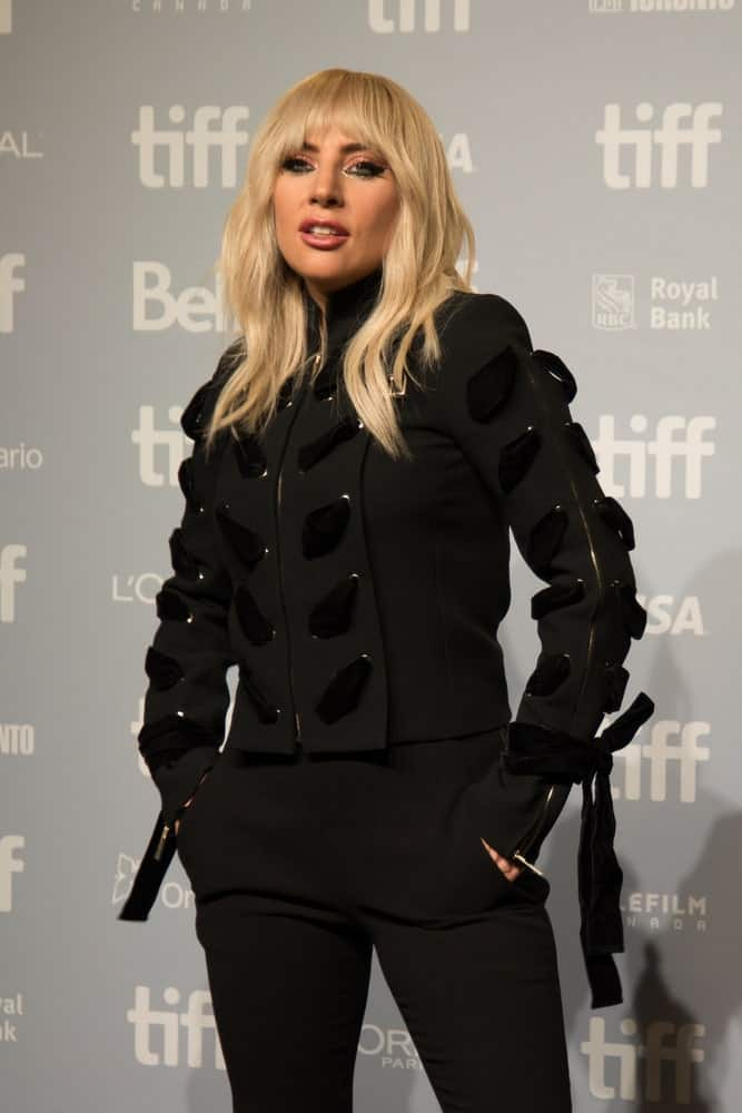 """On September 8, 2017, Lady Gaga attended the Press Conference for her Netflix documentary """"Five Foot Two"""" at the Toronto Film Festival. She came in an all-black detailed outfit to contrast with her loose tousled blond hairstyle with blunt layered bangs."""
