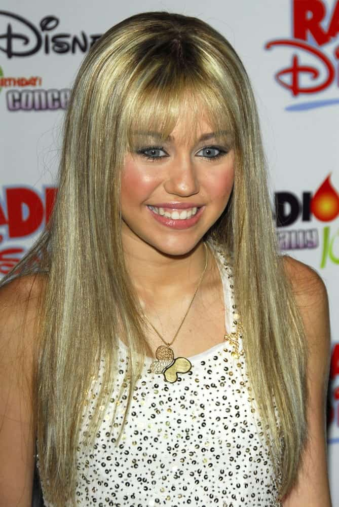 Miley Cyrus wore her iconic Hannah Montana look of straight blond hair with blunt bangs at the Radio Disney Totally 10 Birthday Concert on July 22, 2006 at Anaheim Pond in Anaheim, CA.