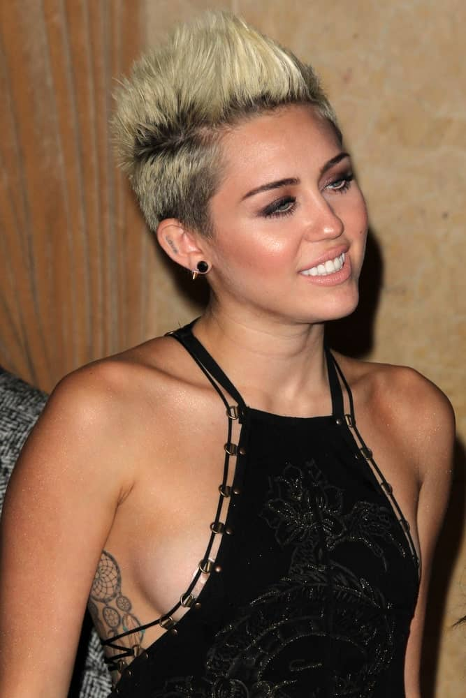 Miley Cyrus wore a stunning black dress that totally complemented her spiked dyed pixie hairstyle when she arrived at the Clive Davis 2013 Pre-GRAMMY Gala at the Beverly Hilton Hotel on February 9, 2013 in Beverly Hills, CA.